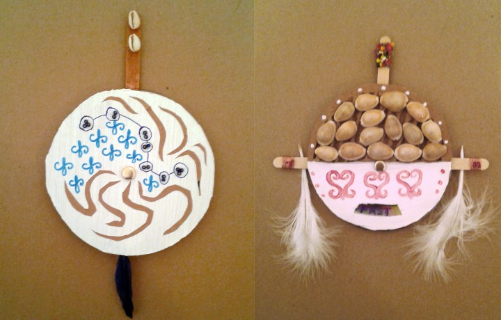 Two unique talismans made from circular cardboard and adorned with shells, decorative marking, beads and feathers